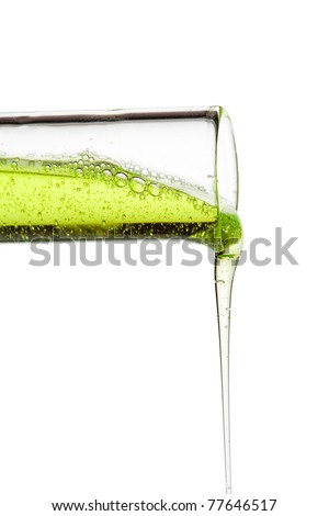 A glass flask with green liquid tilted. The liquid trickling down. - stock photo