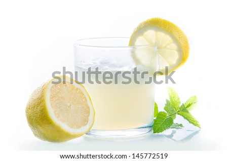 A glass full of lemon juice. - stock photo