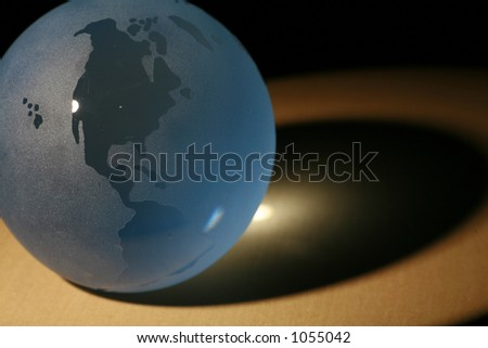 a glass globe in dramatic lighting - stock photo