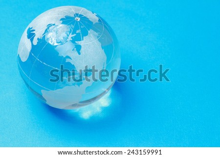 A glass globe, isolated on blue background - stock photo
