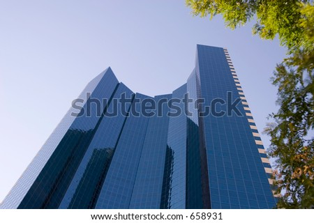 A glass high rise office building in downtown Denver gets lit up by the morning sun. - stock photo
