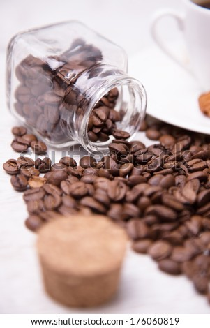 A glass jar and scattered coffee beans