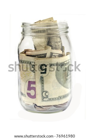 A glass jar contains coin as well as paper currency in denominations of fives and ones. Vertical shot. Isolated on white. - stock photo