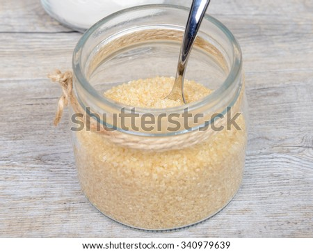A glass jar filled with cane sugar - stock photo