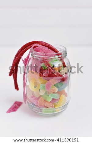 a glass jar full of different candies on a white surface - stock photo