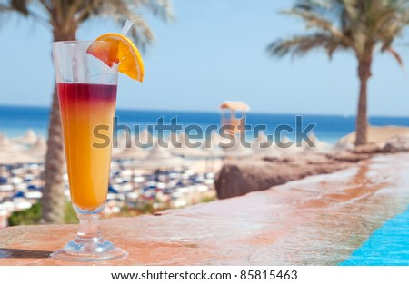 A glass of alcohol fruit cocktail at the pool near sea - stock photo