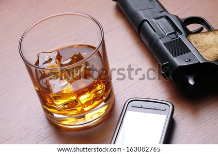A glass of alcoholic drink, a cell phone and a handgun over a wooden table - stock photo