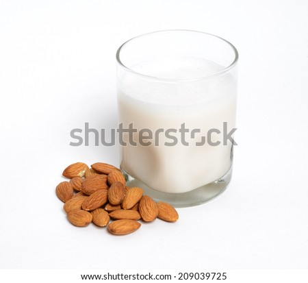 A glass of almond milk with almonds - stock photo
