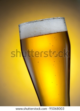 A glass of beer against yellow background