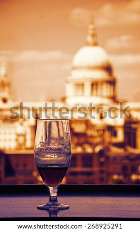 A glass of beer and a view from Tate Modern gallery's cafe on St Paul Cathedral. London, England. Toned photo. - stock photo