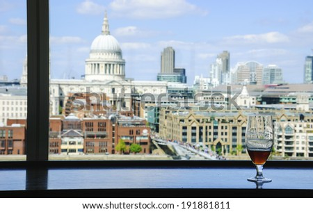 A glass of beer and a view from Tate Modern gallery's cafe on St Paul Cathedral with Millennium Bridge over Thames river. London, England. Reflections. - stock photo