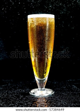 A glass of beer isolated against a black background - stock photo