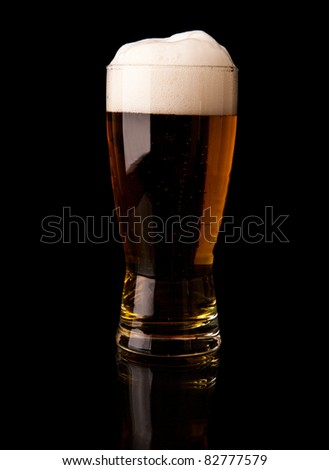 a glass of beer on a black background - stock photo