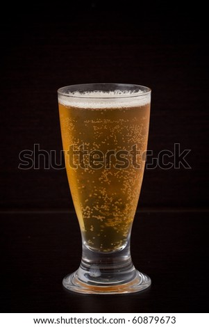 A glass of beer on the wood background. - stock photo