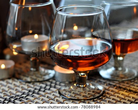 a glass of brandy and a candle, horizontally - stock photo