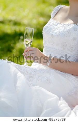 A glass of champagne in the hand of bride in portrait orientation, focused to glass - stock photo