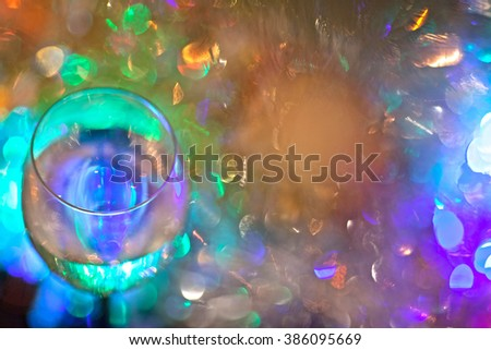 a glass of champagne on a background of colored Christmas lights on the tree garlands (the bright light from Christmas light on the Christmas tree). Abstraction