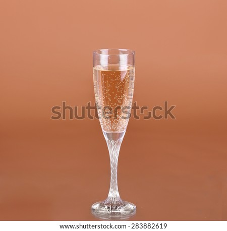 a glass of champagne on a beige background - stock photo