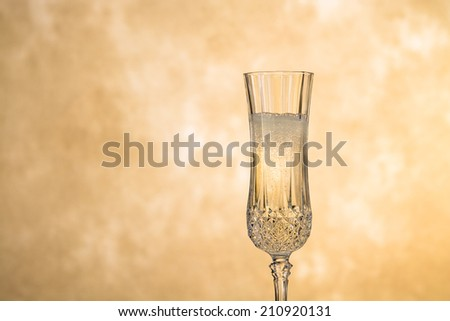A glass of champagne poised against a gold, mottled background. Room for copy on left side of glass. - stock photo