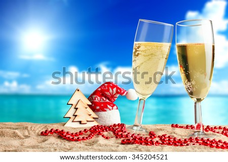 a glass of champagne with elements of the new year on the sand on the sea background - stock photo
