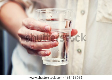 A glass of clean mineral water in woman's hands. Concept of environment protection, healthy drink.