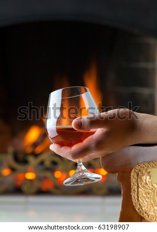 A glass of cognac on the background of a burning fireplace - stock photo