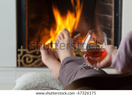 A glass of cognac on the background of a burning fireplace with a brass openwork lattice - stock photo