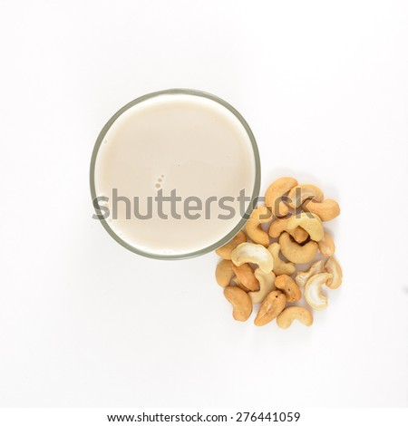 A glass of cold cashew milk next to a pile of cashews isolated on a white background.  View point is from above the glass. - stock photo