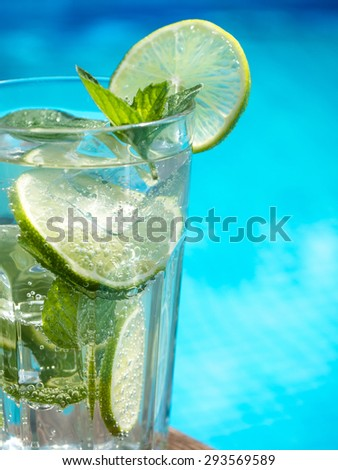 A glass of cold lime and mint drink near a swimming pool - stock photo