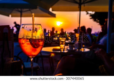 A glass of cold orange cocktail at the sunset on the table of a beach bar at the sunset, with blurry people around having refreshments or partying on a summer evening, with copy space for text - stock photo