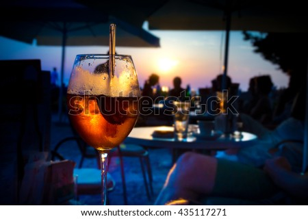 A glass of cold orange cocktail at the sunset on the table of a beach bar at the sunset, with blurry people in the background on a summer evening, with copy space for text. Retro artistic edit. - stock photo