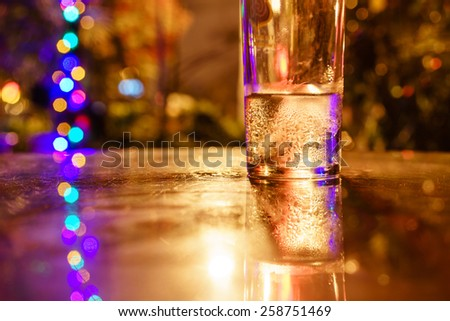 A glass of cold water on table at night with bokeh - stock photo