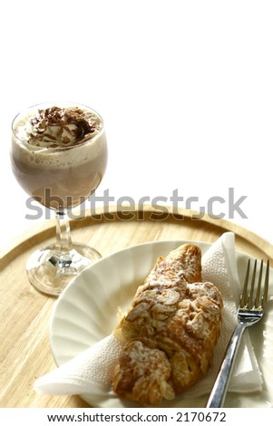 A glass of  delicious hot chocolate/mocha coffee with swirl of cream and a light dusting of chocolate and a hot almond croissant on wooden mat. - stock photo