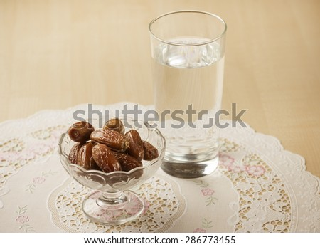 A glass of drinking water and date fruits - a food that is consumed before breaking fast during holy month of Ramadan. - stock photo