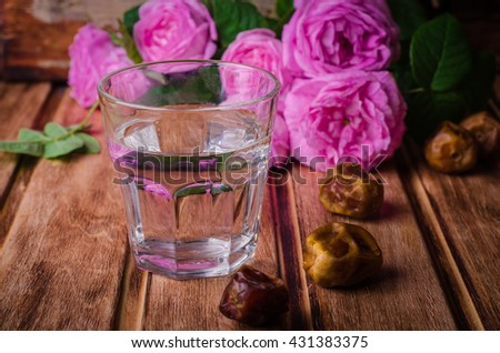 A glass of drinking water and date fruits - a food that is consumed before breaking fast during holy month of Ramadan. Selective focus - stock photo
