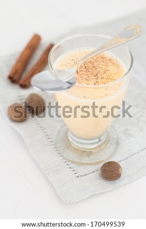 A glass of eggnog on a napkin garnished with cinnamon sticks and nutmeg - stock photo