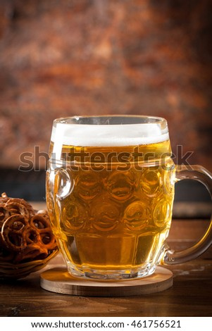 A glass of fresh cold light beer with pretzel and wheat in a bar and a dark pub