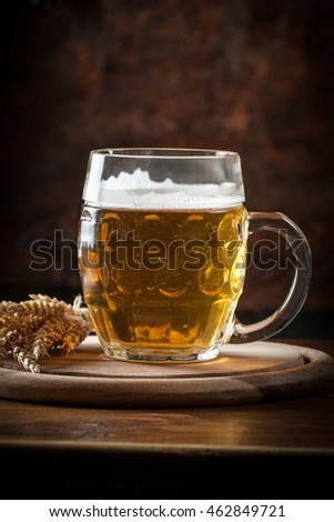 A glass of fresh cold light beer with wheat and barley in a bar and a dark pub