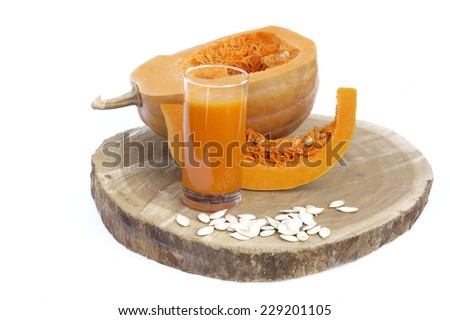 A glass of fresh pumpkin vegetable juice isolated on white and wood background - stock photo