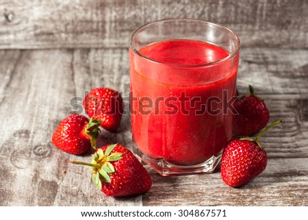 A glass of fresh strawberry smoothie on a wooden background. Summer drink and refreshment organic concept. - stock photo