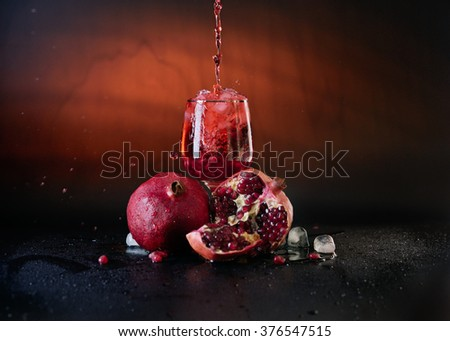 A glass of  juice with a splash and some pieces of pomegranate on a black background. - stock photo