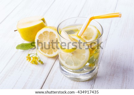 A glass of lemon-apple fruit with water on a wooden white table. Near lemon and linden flower. Tubule for cocktail.