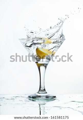 A glass of martini and slice of lemon, a splash and spray on a light background, selective focus - stock photo