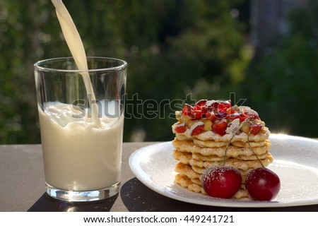 A glass of milk and a waffle cake with banana and sweet cherry - stock photo