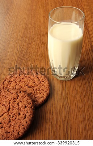 A glass of milk and chocolate cookies on wooden background. - stock photo