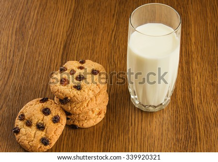 A glass of milk and cookies on wooden background. - stock photo