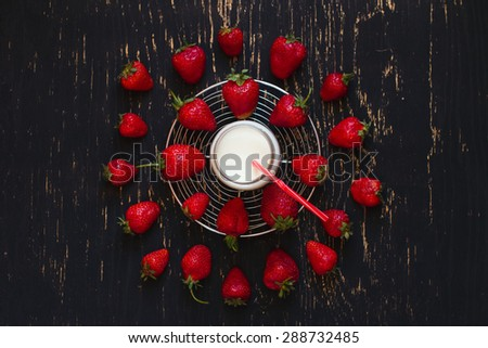 A glass of milk and fresh strawberries on a dark wooden background - stock photo