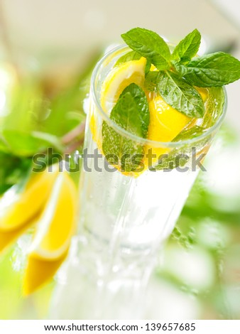a glass of mineral water with lemon and mint - stock photo
