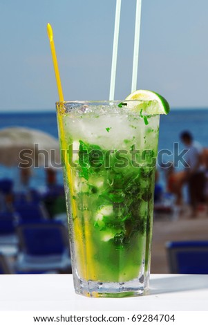 A glass of mojito cocktail with mint on beach and sky background - stock photo