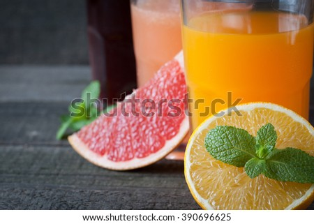 A glass of orange juice, mint and slices of orange on wooden background. Healthy drink concept. Vitamins and diet. Shake and smoothie.